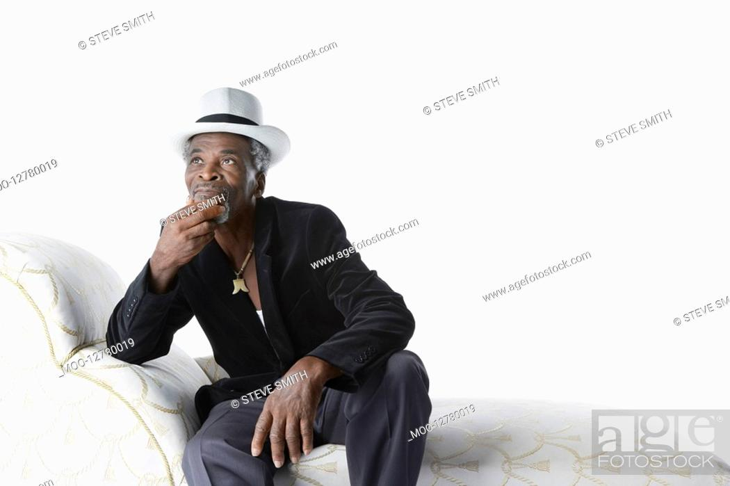 Stock Photo: Man in Fedora on Chaise Lounge.