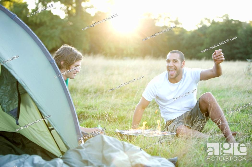Stock Photo: Two young men sitting next to a tent, having a barbecue.