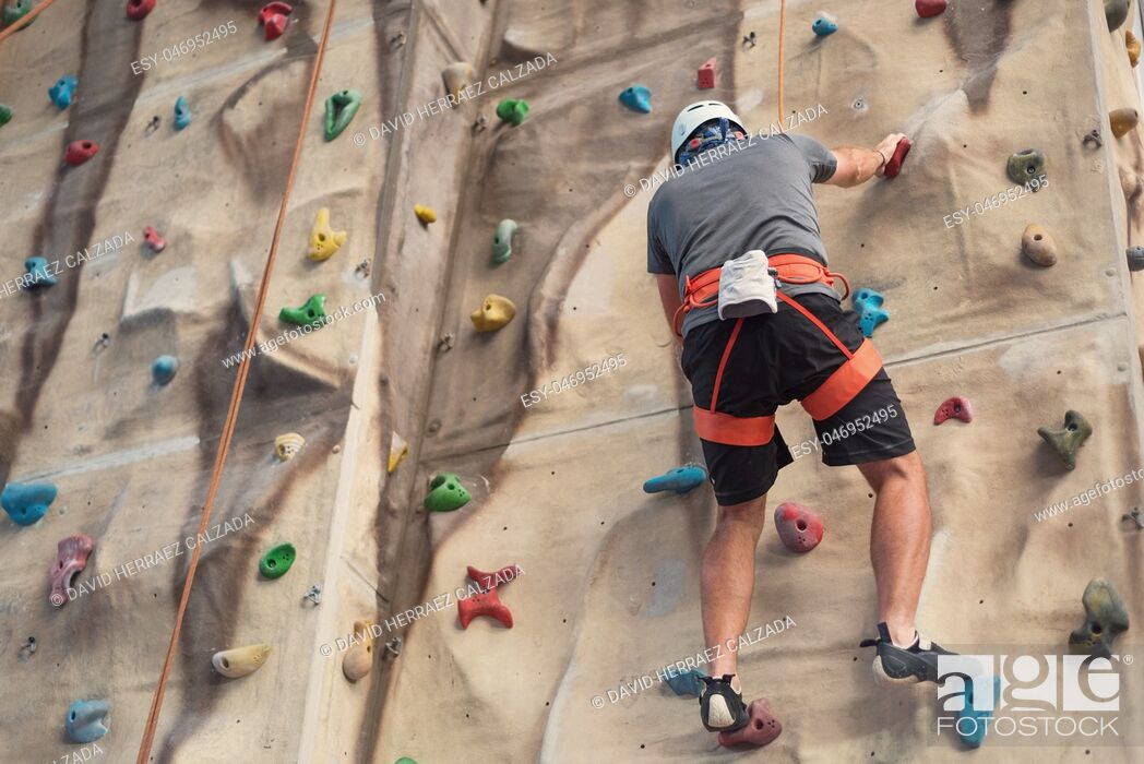 Stock Photo: Young man practicing rock climbing on artificial wall indoors.