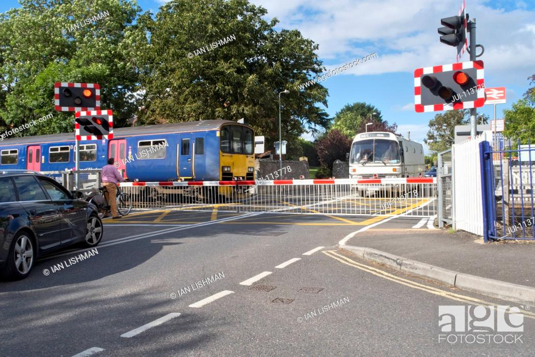 Stock Photo: Railway train crossing road with level crossing and bus and car waiting.