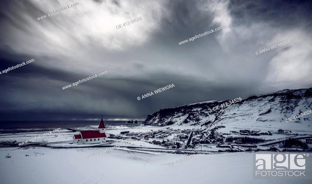 Stock Photo: Church in remote snow covered landscape below stormy sky, Vik, Iceland.