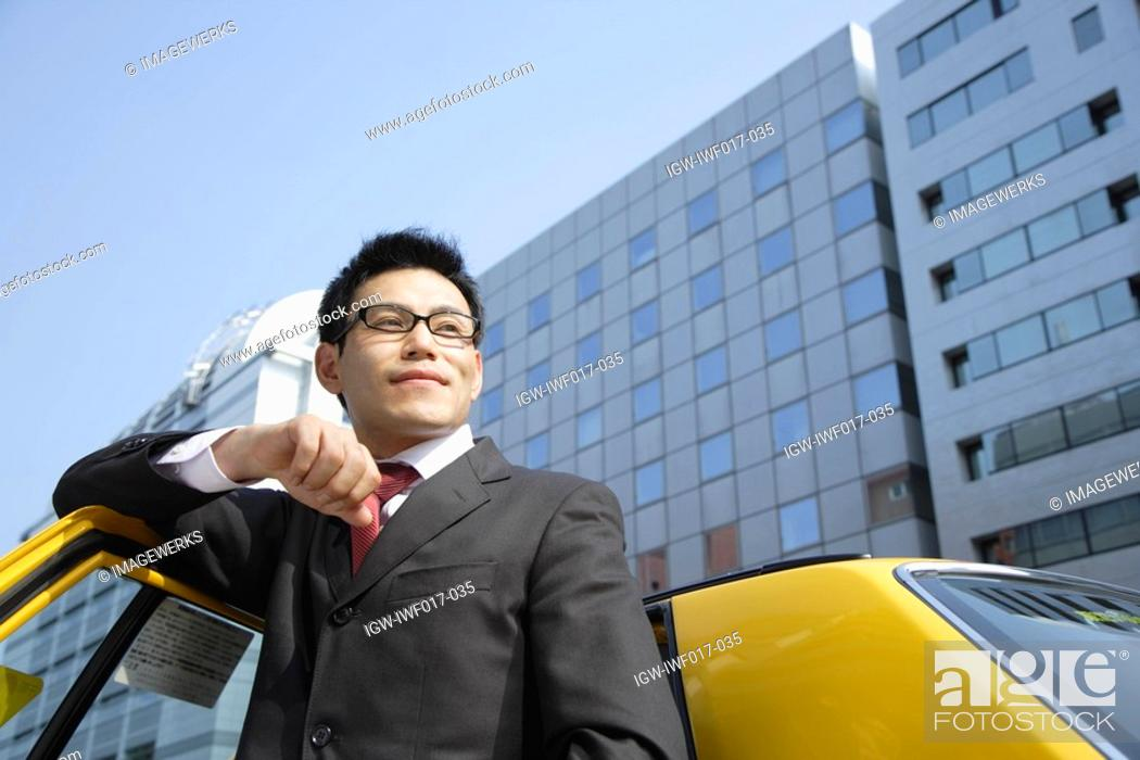 Stock Photo: Man leaning against car door, portrait.