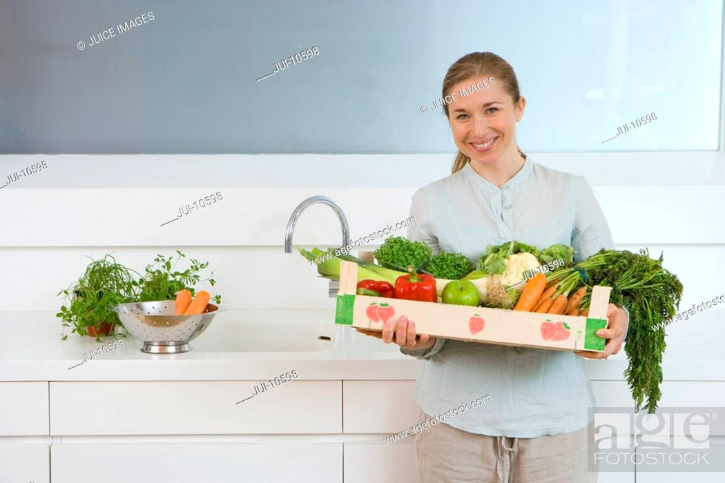 Stock Photo: Woman in kitchen with box of vegetables, smiling, portrait.