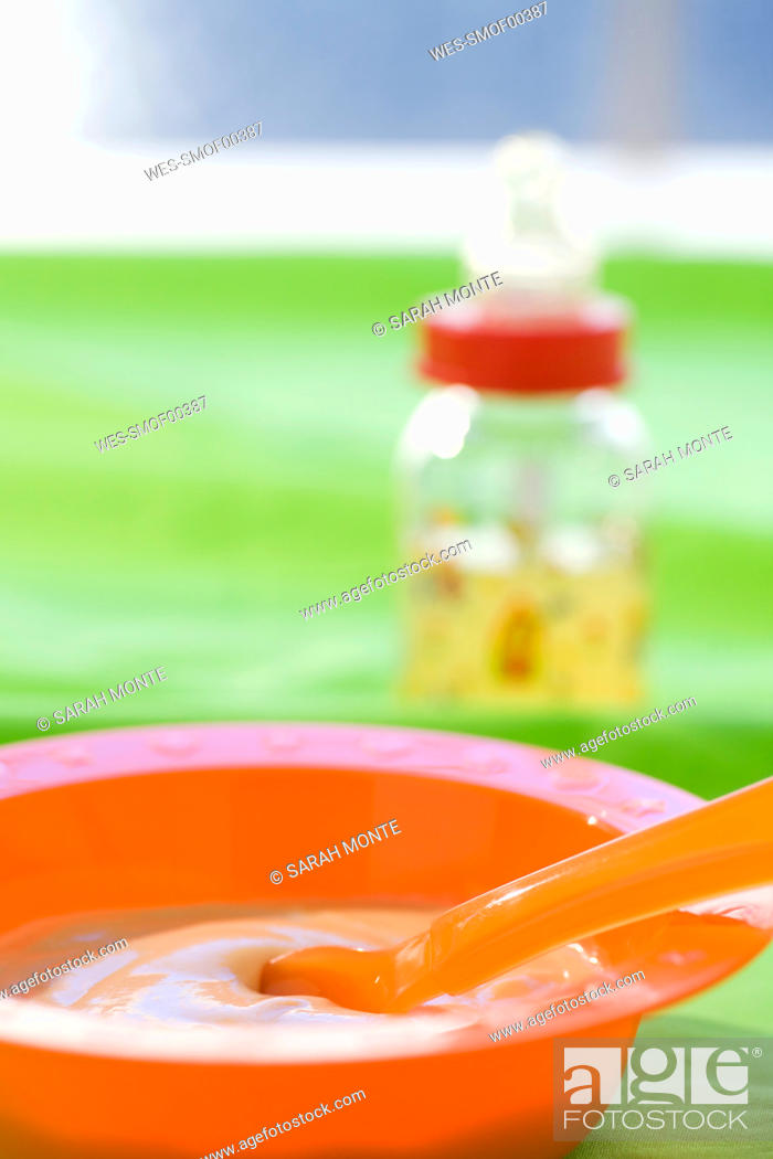 Stock Photo: Baby food in bowl with baby bottle in background.