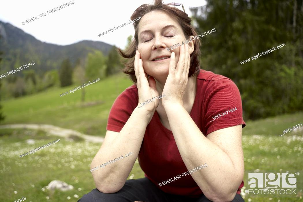 Stock Photo: Mature woman in countryside with eyes closed. Bad Tölz, Upper bavaria, Germany.