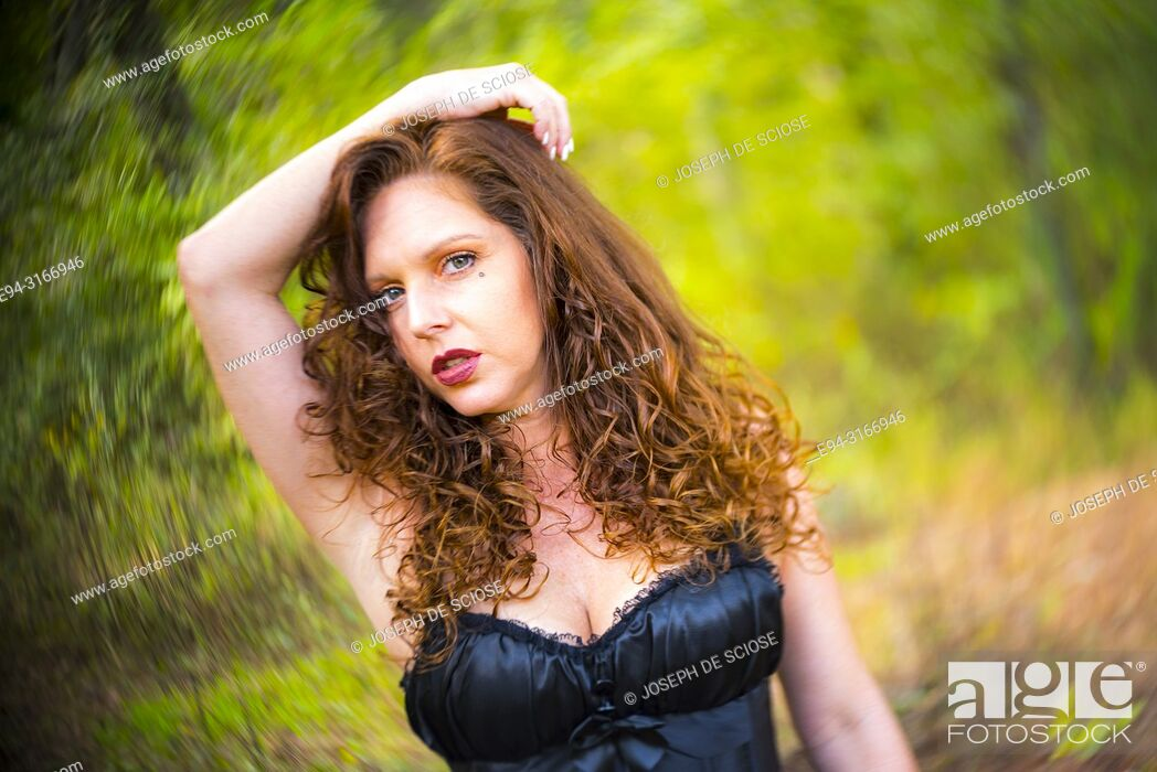 Stock Photo: A pretty 39 year old redheaded woman wearing a black corset and a tutu looking at the camera, outdoors.