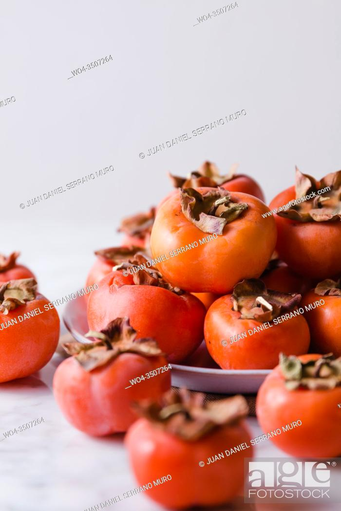 Stock Photo: Some persimmons in a plate on a marble surface. Front vertical shot.