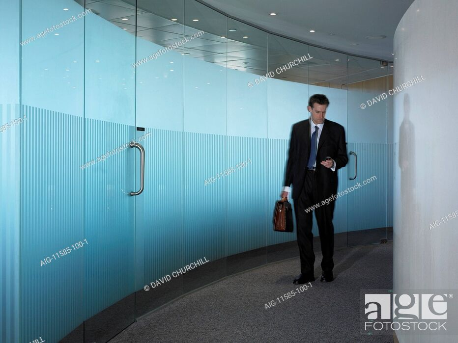 Stock Photo: Office life and interiors (model released). Businessman in corridor using mobile phone about to leave.