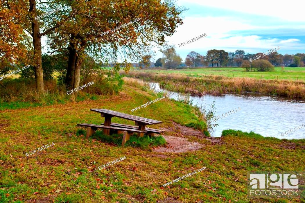 Stock Photo: wooden table and benches by river.
