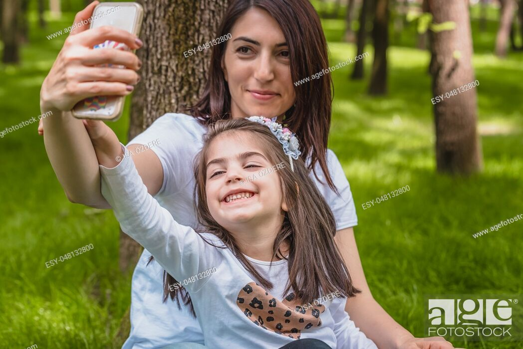 Imagen: Young mom and little girl takes selfie together. Happy mother and daughter moments with love and natural emotion. Photo of young mother and her daughter having.