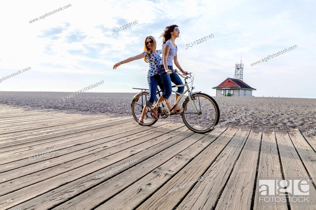 Stock Photo: Two girls riding double on a single bike on a beach boardwalk; Toronto, Ontario, Canada.