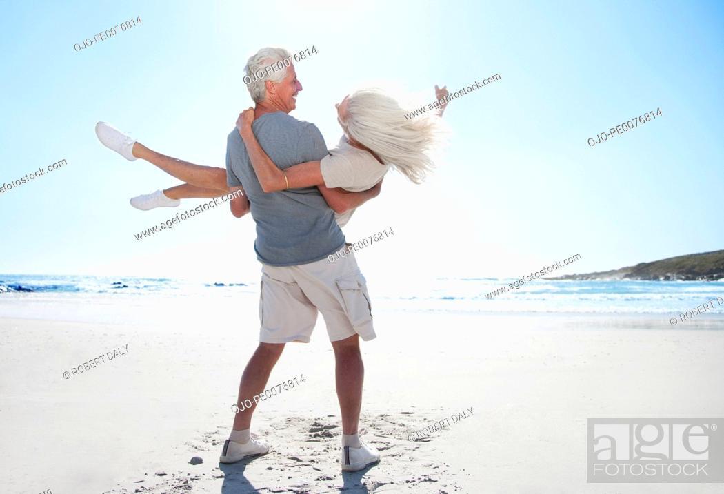 Stock Photo: Man spinning woman on beach.