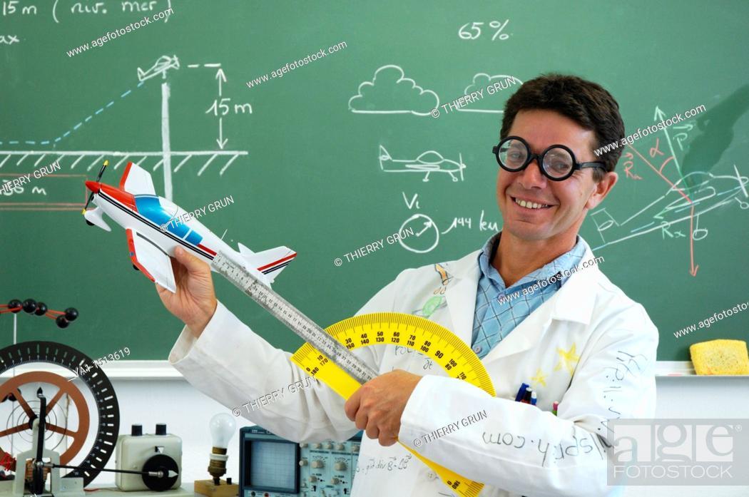 Stock Photo: Funny school teacher explaining motorized flight with model plane.