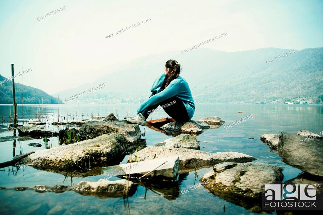 Stock Photo: Young woman sitting on rock looking out over Lake Mergozzo, Verbania, Piemonte, Italy.