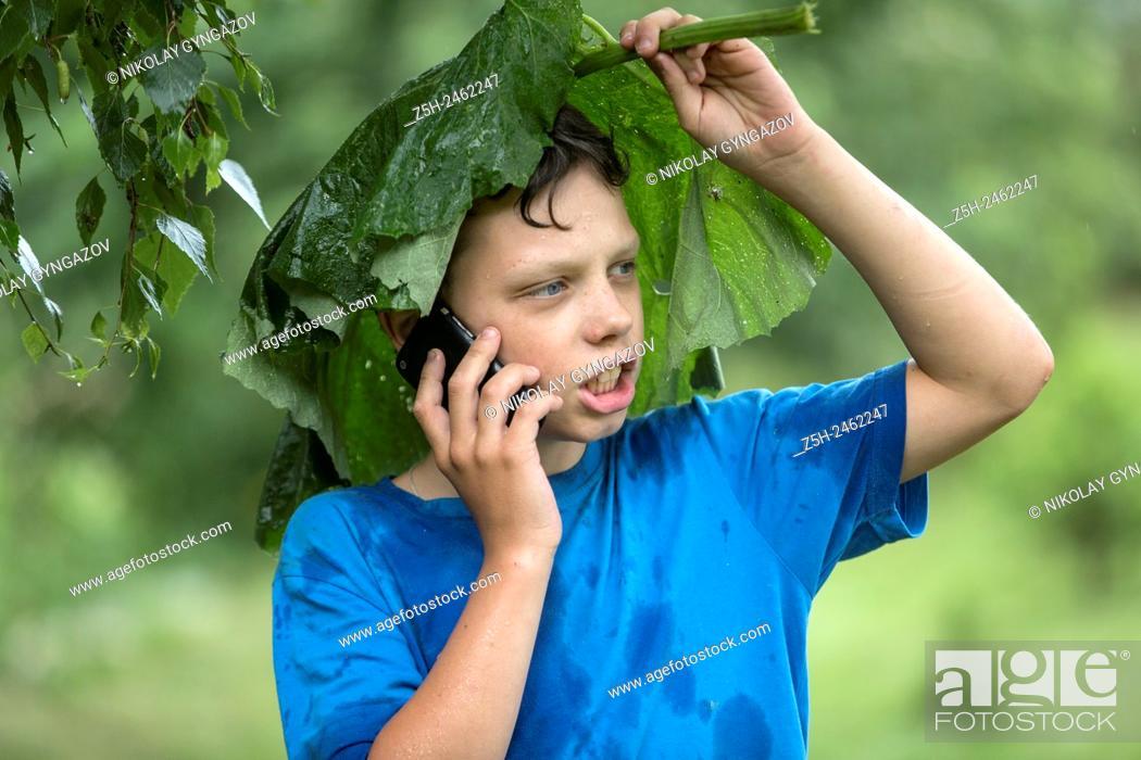 Stock Photo: Russian Federation. Belgorod region. The boy in the rain uryvshiysya leaves of the plant.