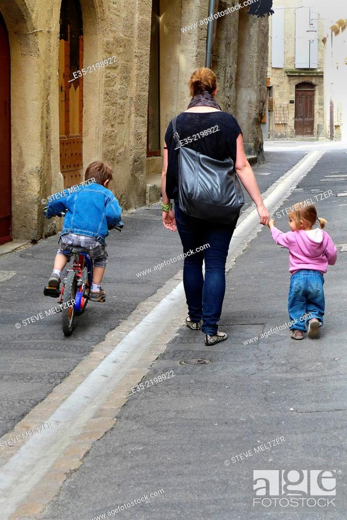 Stock Photo: A mother walks with her children.