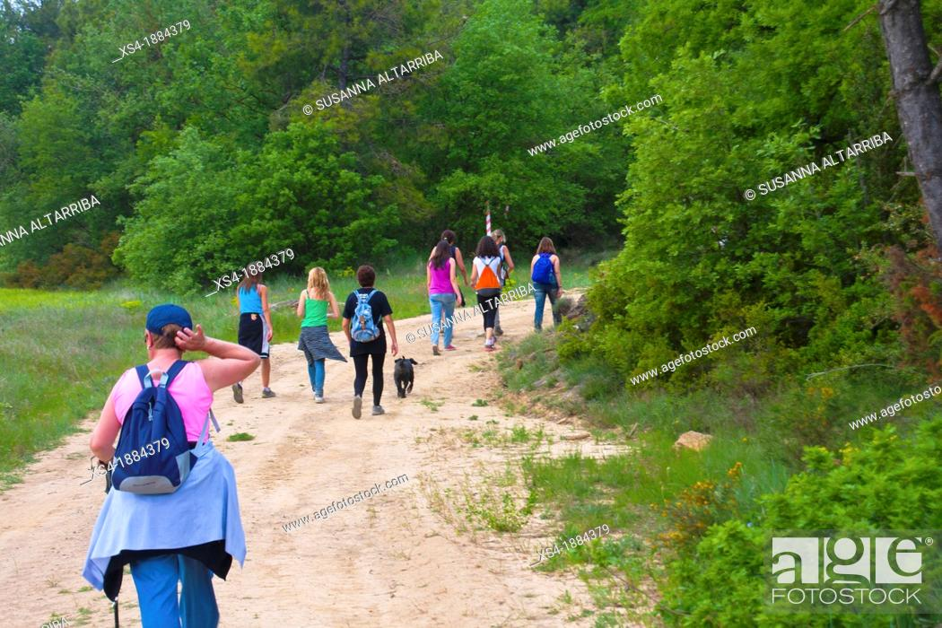 Imagen: Group of 9 women hiking through the countryside in spring time with backpack and a dog  Photo taken in Pinos, Lleida, Spain, Europe.