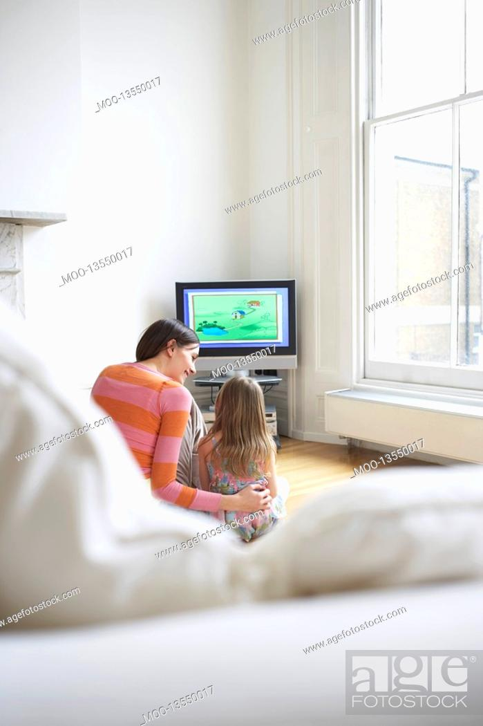 Stock Photo: Mother and daughter 5-6 watching cartoons in television back view.