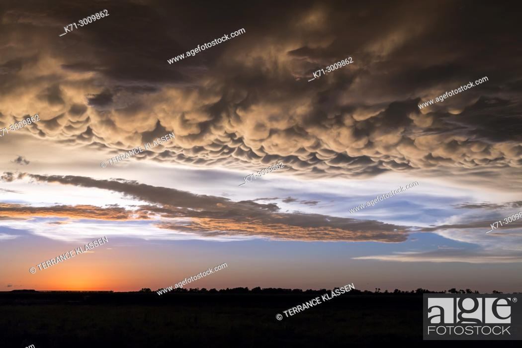 Stock Photo: A clearing storm and clouds on the prairies at sunset near Winkler, Manitoba, Canada.