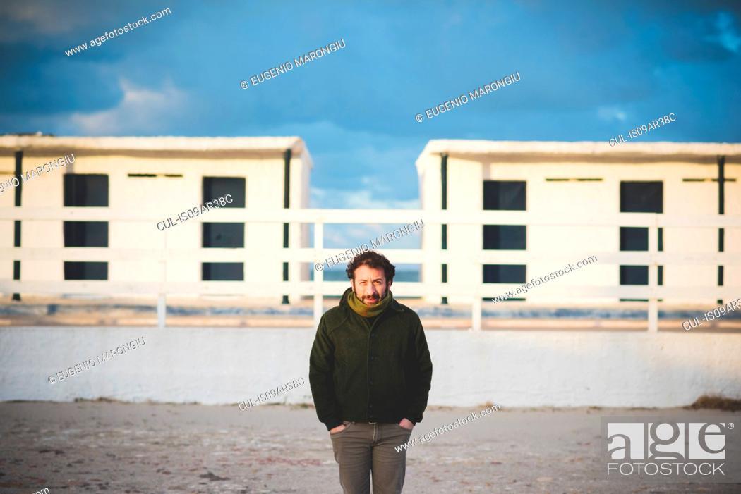 Photo de stock: Portrait of mid adult man in front of beach huts, Sorso, Sassari, Sardinia, Italy.