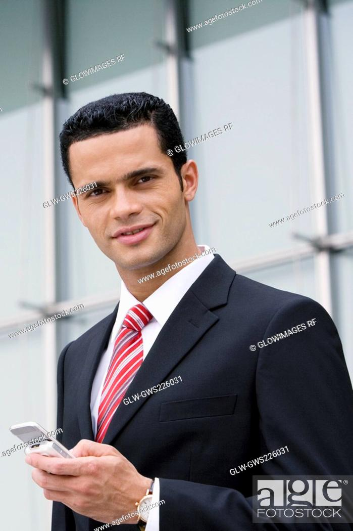 Stock Photo: Portrait of a businessman holding a mobile phone and smiling.