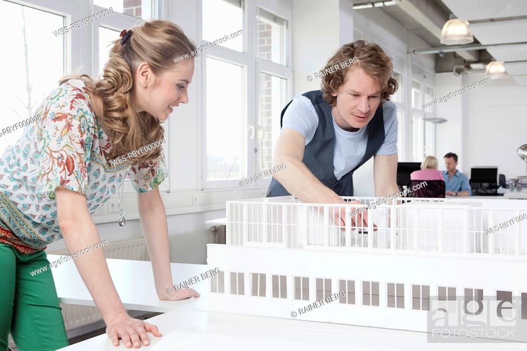 Stock Photo: Germany, Bavaria, Munich, Architects looking at architectural model, colleagues working in background.