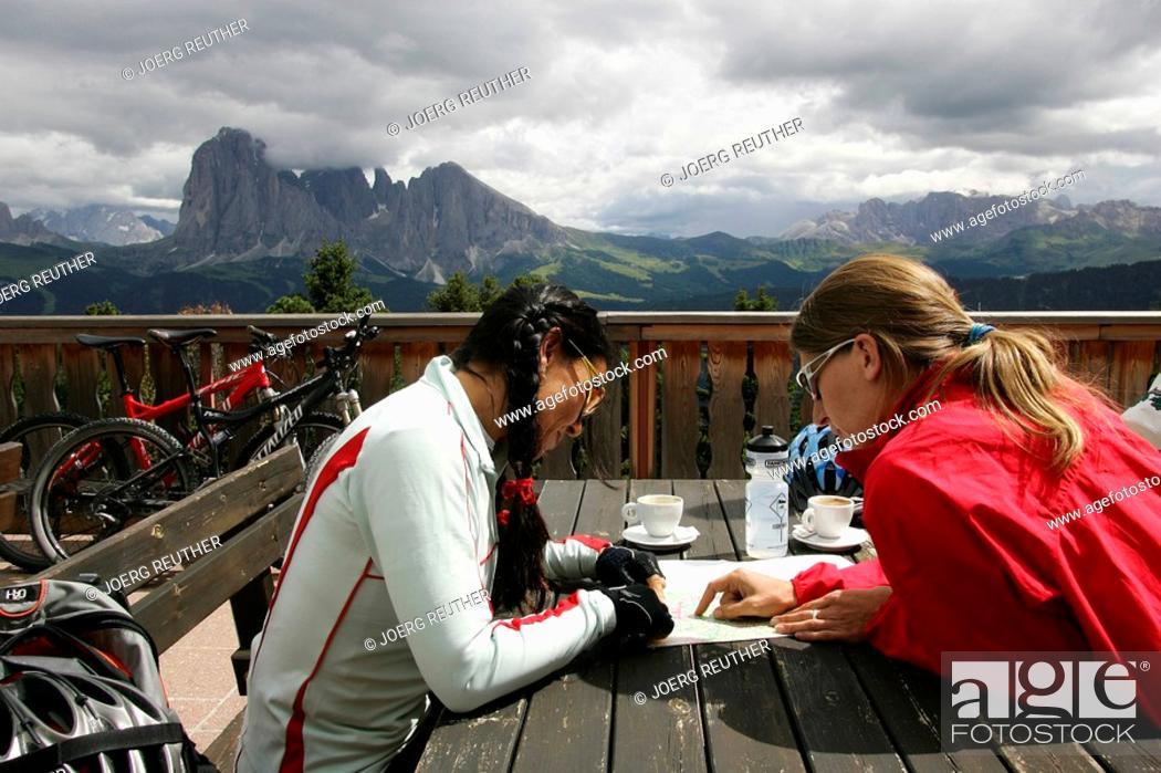 Stock Photo: Female mountain bikers taking a break at Raschoetz Restaurant, Mts. Marmolada, Langkofel, Plattkofel and Rosengarten in the background, Dolomites.