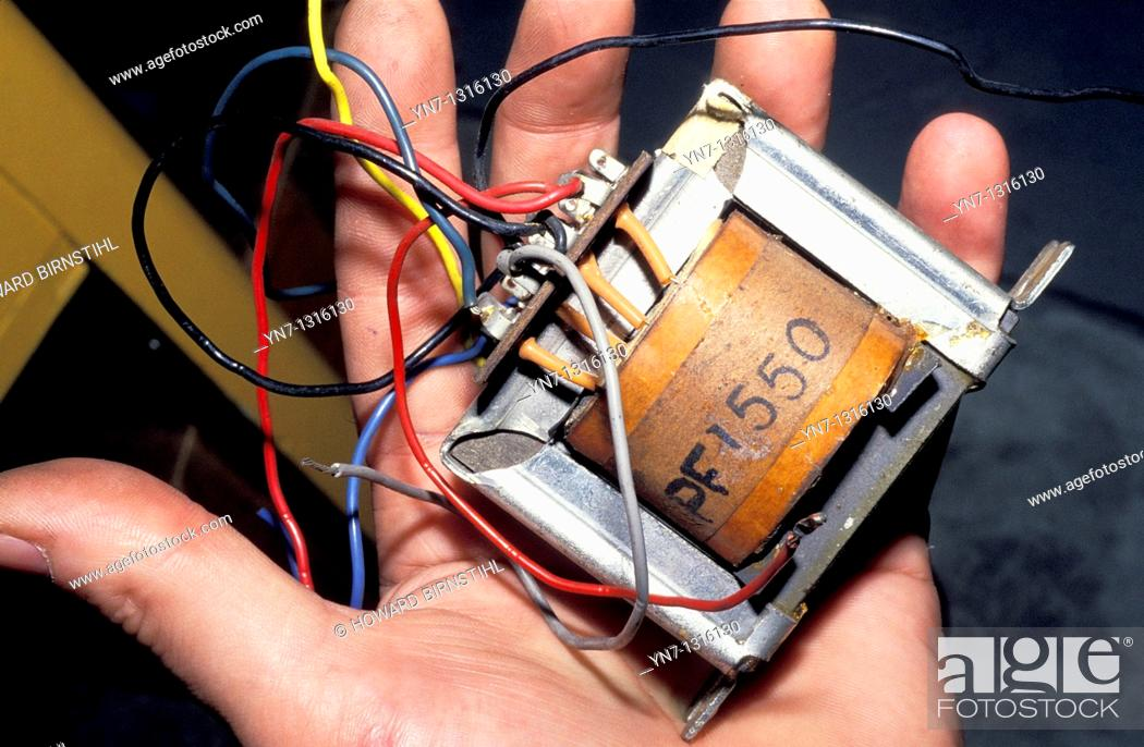Stock Photo: hand holding old fashioned transformer with wires protruding.