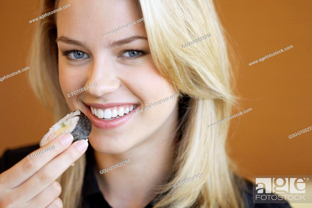 Stock Photo: Young woman eating sushi.