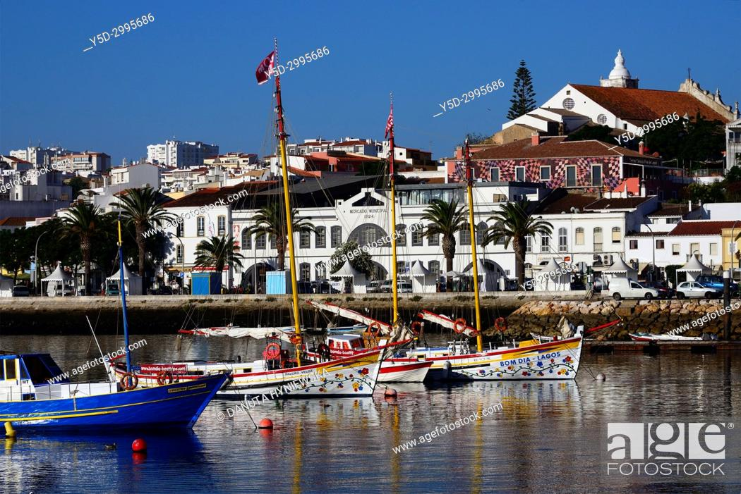 Stock Photo: Boats moored in the harbour, in background old town with historic food market, Ciencia Viva - cultural center and Sao Sebastiao church, Lagos, Algarve, Portugal.