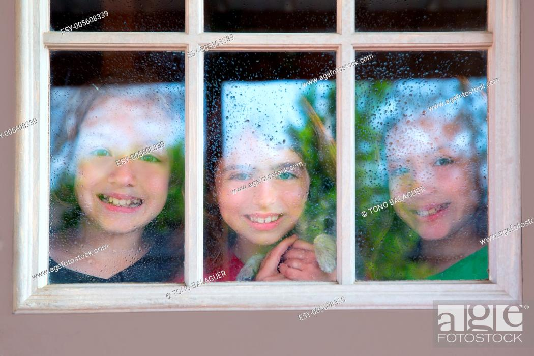 Stock Photo: three sister friends looking through the window with a pup and raindrops.