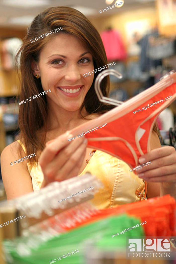 Stock Photo: Portrait of a young woman holding underwear in a clothing store.