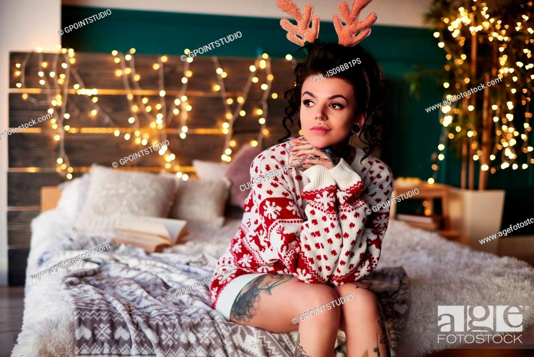 Stock Photo: Young woman sitting on edge of bed, wearing christmas jumper and antlers, thoughtful expression.