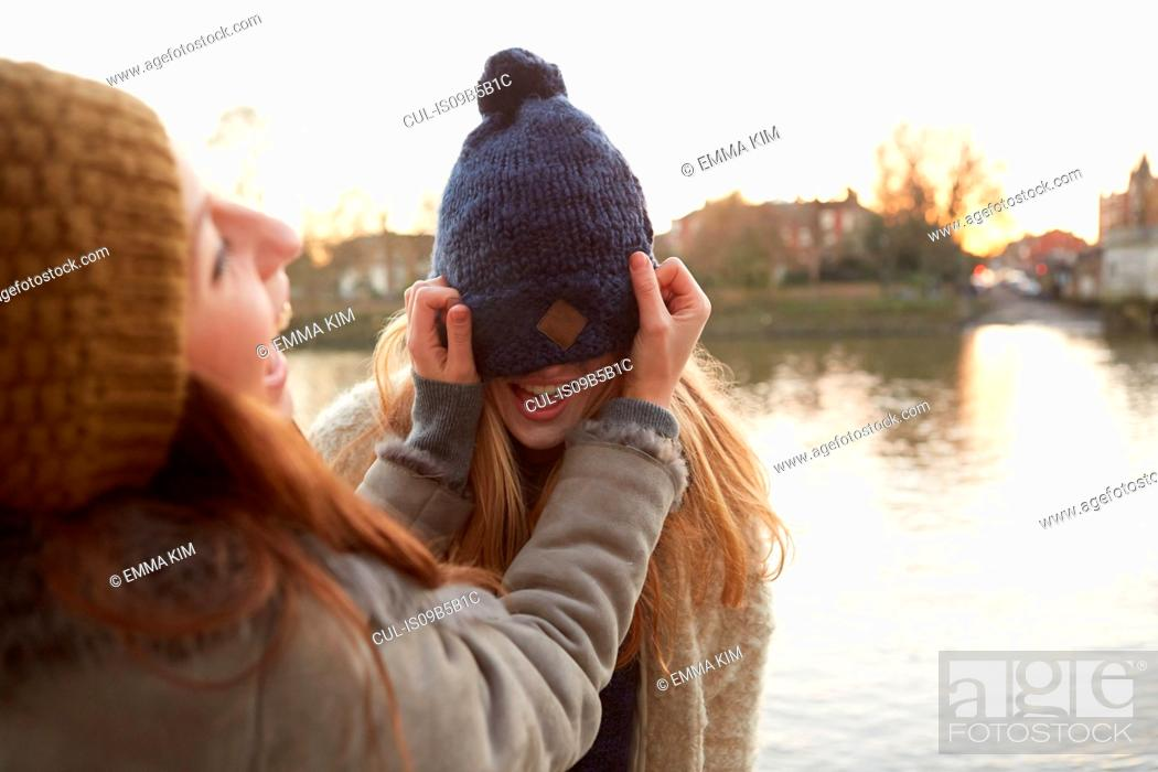 Stock Photo: Young woman putting knitted hat on friend, hat covering eyes, laughing.