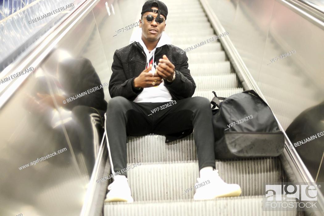 Stock Photo: young man sitting on escalator, in Munich, Germany.