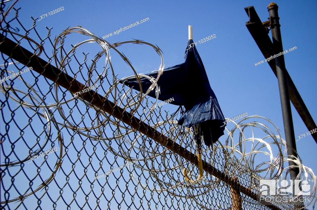 Stock Photo: An umbrella stands atop a barbed wire fence.