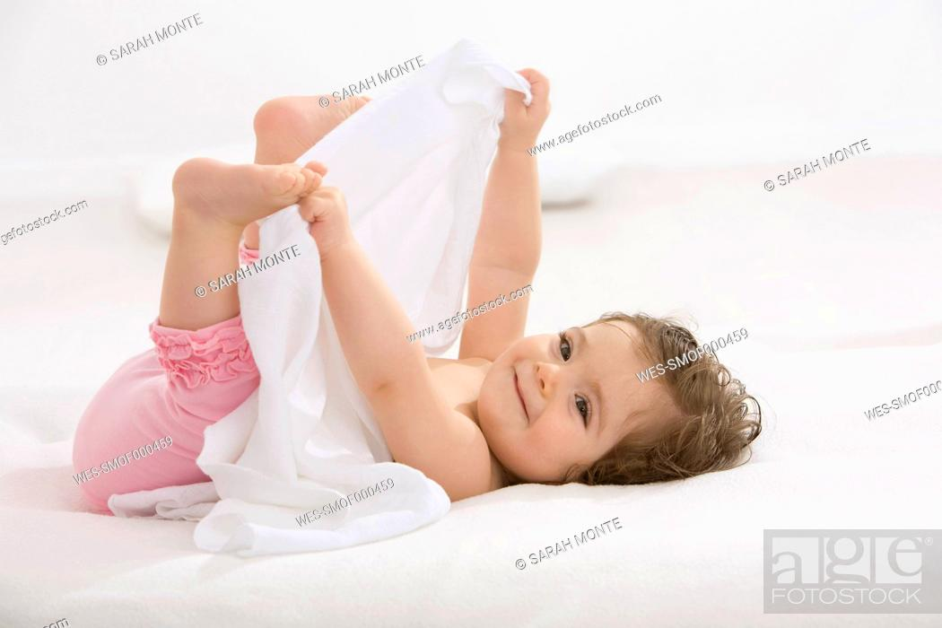 Stock Photo: Baby girl lying on back and holding toes, smiling.