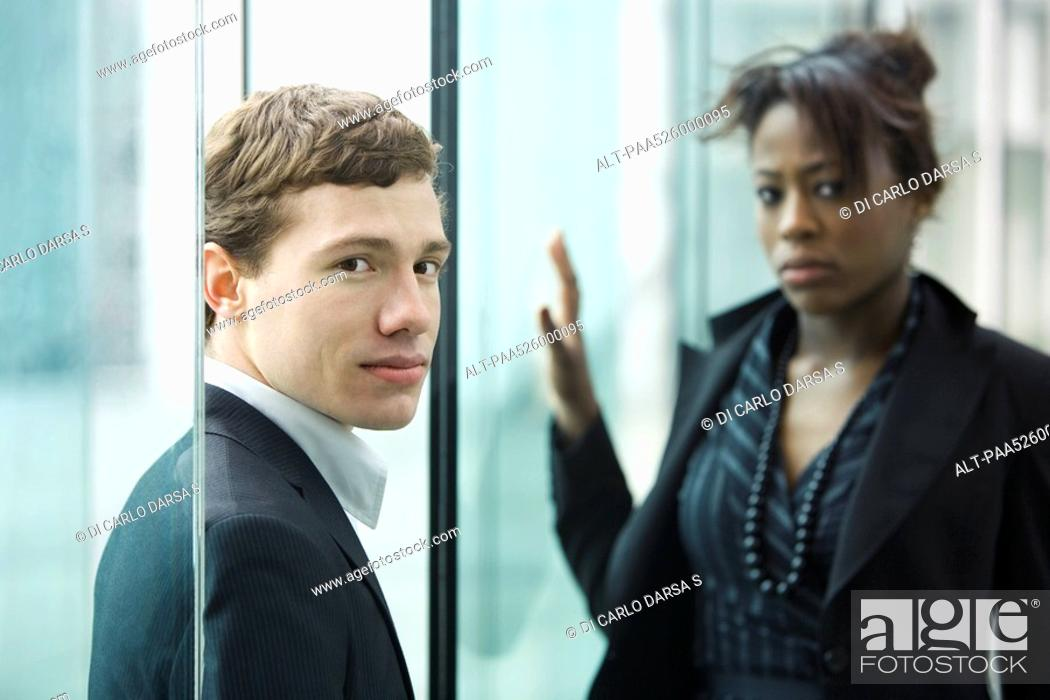 Stock Photo: Businessman and businesswoman looking at camera with uncertainty.