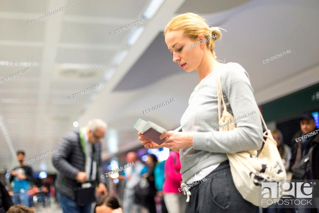 Stock Photo: Casualy dressed woman checking flight informations on airplane ticket while waiting for her flight at airport.