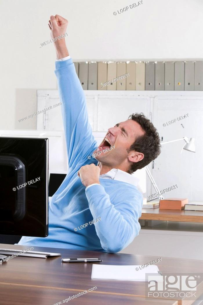 Stock Photo: Germany, Munich, business man in office, cheering, portrait.