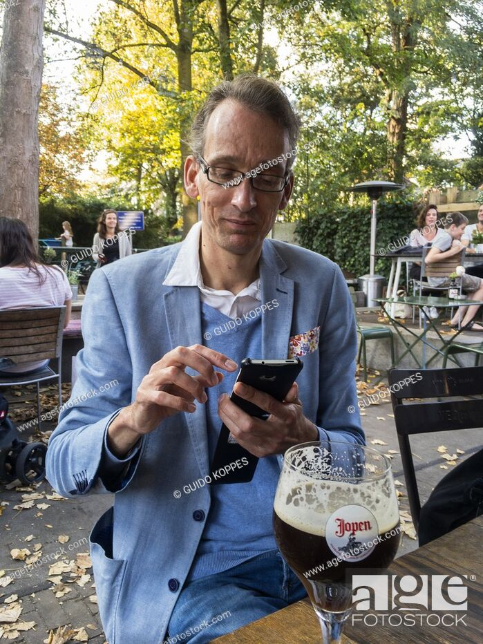Stock Photo: Tilburg, Netherlands. Mid adult male using his smartphone while drinking a beer and having a conversation. Friendship is often celebrated in cafe's and.