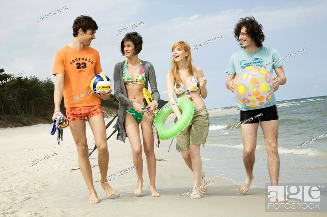 Stock Photo: Four friends walking on the beach with sport and beach accessories .