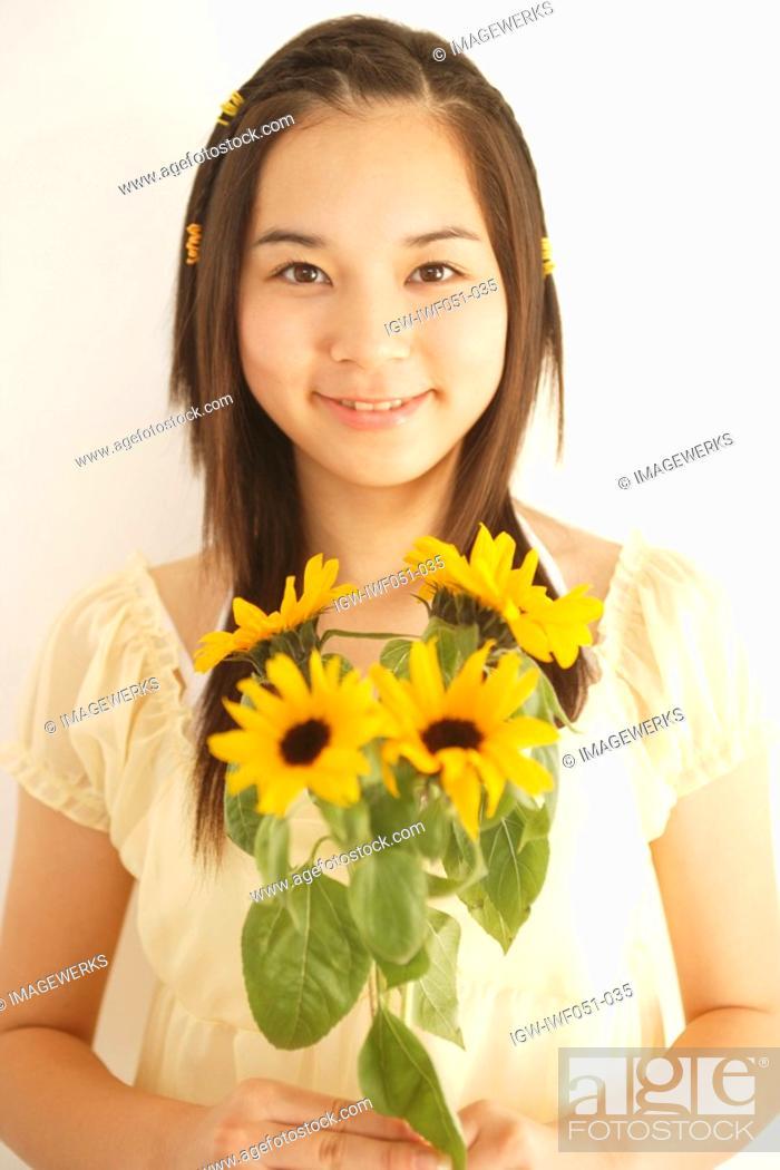 Stock Photo: Teenage girl 14-15 with flowers, portrait.