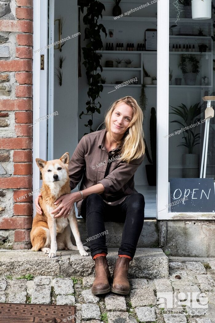 Stock Photo: Smiling female owner of plant shop sitting on steps outside her store, a dog sitting next to her.