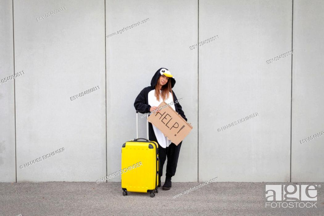 Stock Photo: Young woman, with penguin costume and yellow suitcase, has to travel due to global warming. Symbolizes a sad penguin who has to leave his homeland because of.