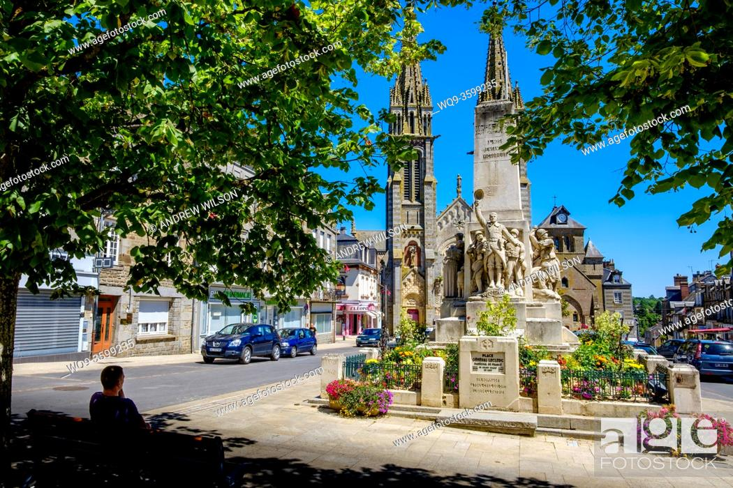 Stock Photo: Notre-Dame de la Ferté-Macé, Lower Normandy, France with the town's war memorial in the foreground.