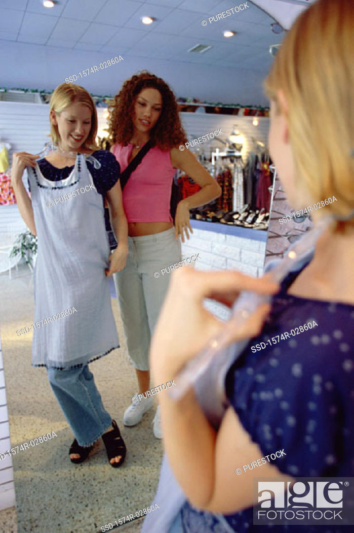 Stock Photo: Two young women trying on clothes in a clothing store.