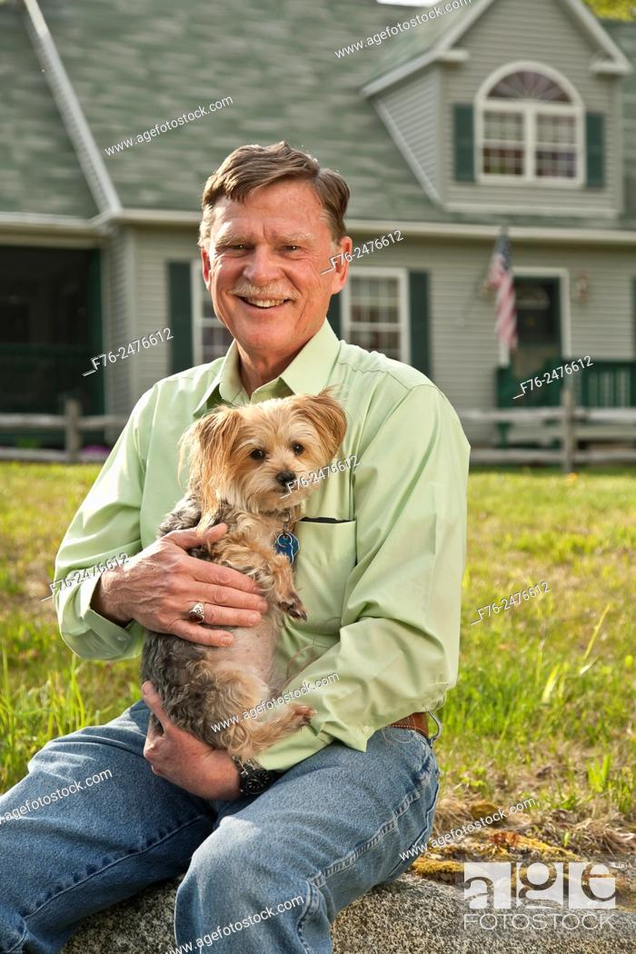 Stock Photo: Man in blue jeans, sitting in front of his home, holding his small yorkshire terrier.