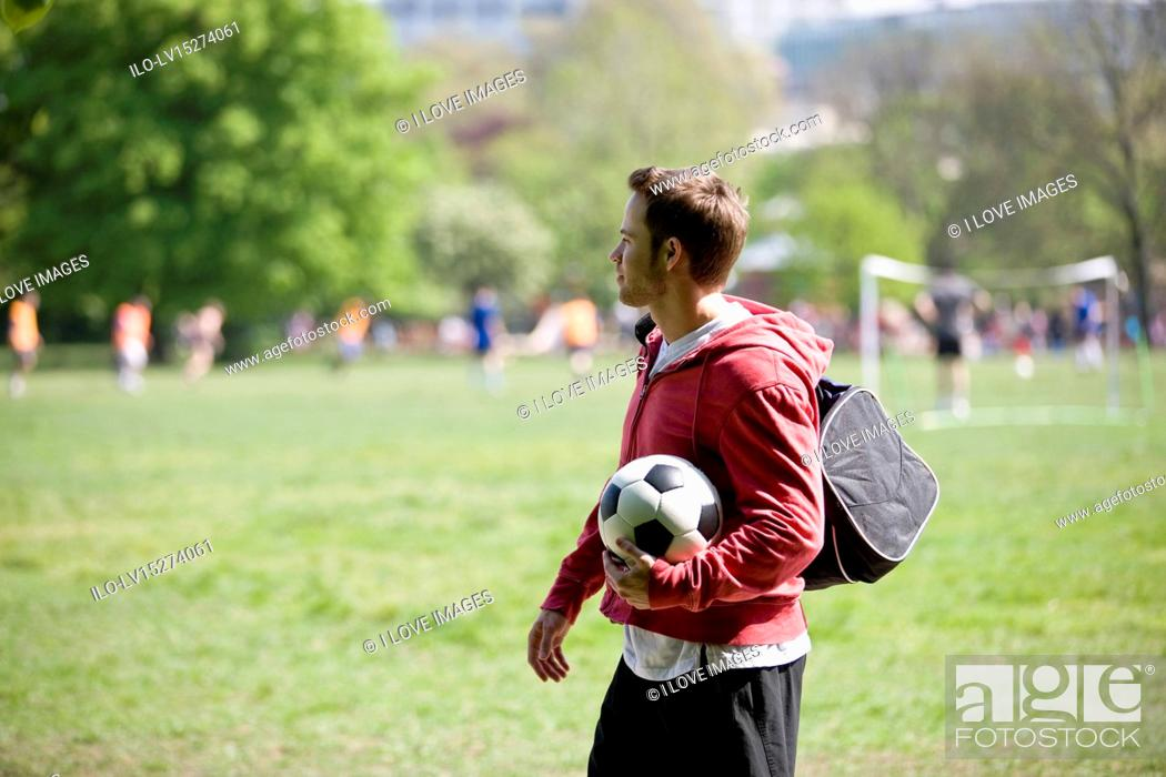 Stock Photo: A young man standing in the park, carrying a football and a sports bag.