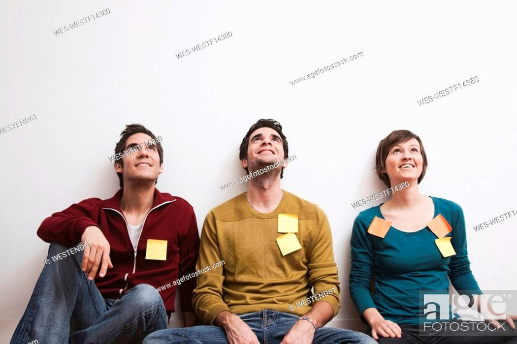 Stock Photo: Men and women sitting against wall, looking up.